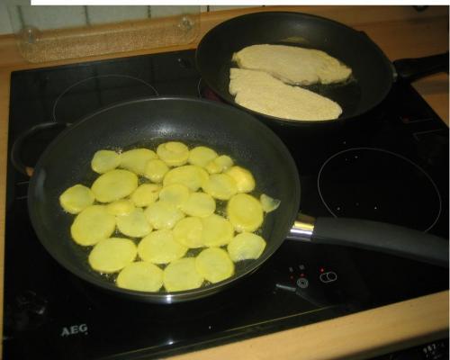 Fertigschnitzel mit Bratkartoffel in der Pfanne